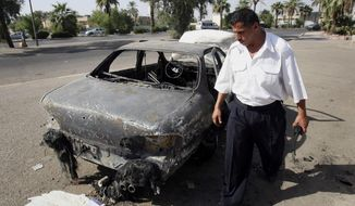 FILE - This Sept. 25, 2007 file photo shows an Iraqi traffic policeman inspects a car destroyed by a Blackwater security detail in al-Nisoor Square in Baghdad, Iraq. After years of delays, four former guards from the security firm Blackwater Worldwide are facing trial in the killings of 14 Iraqi civilians and the wounding of 18 others in bloodshed that inflamed anti-American sentiment around the globe. Whether the shootings were self-defense or an unprovoked attack, the carnage of Sept. 16, 2007 was seen by critics of the George W. Bush administration as an illustration of a war gone horribly wrong. A trial in the nearly 7-year-old case is scheduled to begin with jury selection on Wednesday, barring last-minute legal developments. (AP Photo/Khalid Mohammed, File)