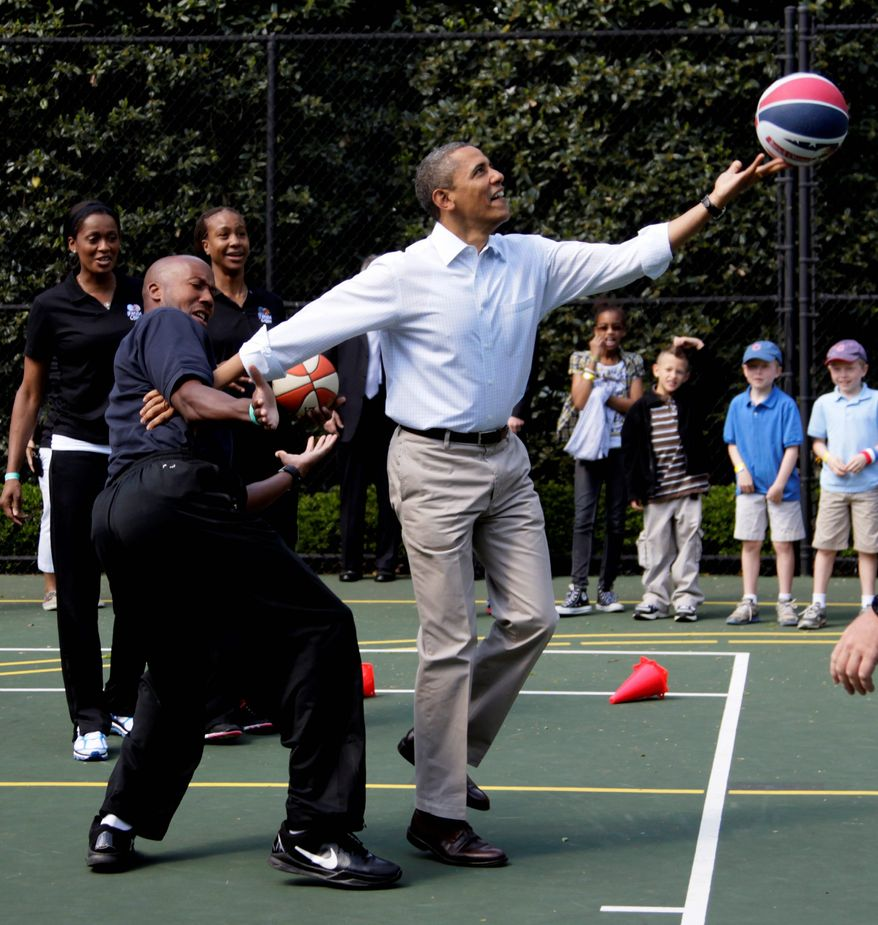 President Barack Obama plays basketball with former NBA basketball player Bruce Bowen during the annual White House Easter Egg Roll, Monday, April 9, 2012, at the White House in Washington. (AP Photo/Carolyn Kaster)
