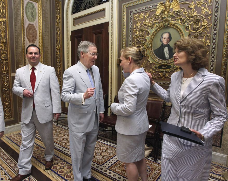 """**FILE** Members of the Senate get together for """"Seersucker Thursday"""" on Capitol Hill in Washington on June 23, 2011. The tradition was started by former Mississippi Sen. Trent Lott, who encouraged colleagues to don the lightweight, striped, summer-friendly fabric to combat the oppressive humidity in the nation's capital. From right are Sens. Lisa Murkowski, Alaska Republican, Kirsten Gillibrand, New York Democrat, Senate Minority Leader Mitch McConnell of Kentucky and Mike Lee, Utah Republican. (Associated Press)"""