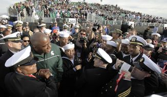 **FILE** Former Michigan State basketball player and NBA great Magic Johnson poses with members of the Navy as he arrives for the Carrier Classic NCAA college basketball game aboard the USS Carl Vinson, Friday, Nov. 11, 2011, in Coronado, Calif. (AP Photo/Gregory Bull)