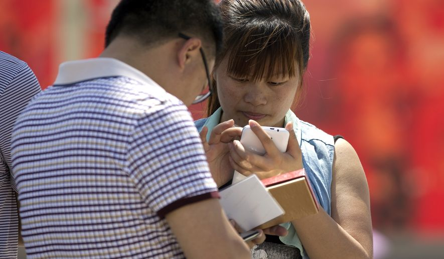 """Chinese people use their smartphone on Tiananmen Square in Beijing on May 28, 2014. China is targeting popular smartphone-based instant messaging services in a month-long campaign to crack down on the spreading of rumors and what it calls """"hostile forces at home and abroad,"""" the latest move to restrict online freedom of expression. (Associated Press)"""