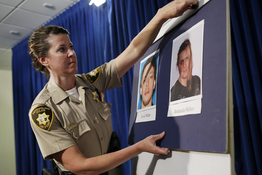 Las Vegas Metropolitan Police Department Officer Laura Meltzer hangs up pictures of suspects Jerad Miller and Amanda Miller before a news conference Monday, June 9, 2014 in Las Vegas. Two police officers were having lunch at a strip mall pizza buffet when the Millers fatally shot them in a point-blank ambush, then fled to a nearby Wal-Mart where they killed a third person and then themselves in an apparent suicide pact, authorities said. (AP Photo/John Locher)