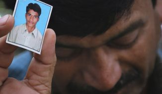Bonath Shekar Naik shows a portrait of his son Rambabu, only one name available, one of the 24 students feared dead during a field trip near the mountain resort town of Manali, at the college premises of VNR Vignana Jyothi Institute of Engineering and Technology, on the outskirts of Hyderabad, India, Monday, June 9, 2014. (AP Photo/ Mahesh Kumar A.)