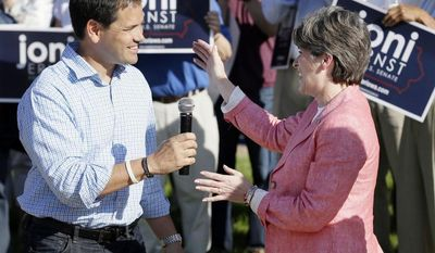 U.S. Sen. Marco Rubio, R-Fla., is greeted by Iowa Republican senatorial candidate Joni Ernst, right, before speaking at a rally with Ernst supporters, Monday, June 2, 2014, in Urbandale, Iowa. (AP Photo/Charlie Neibergall)
