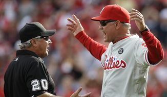 Philadelphia Phillies manager Ryne Sandberg (23) argues a reviewed call at home with umpire Tom Hallion (20) in the sixth inning of a baseball game against the Cincinnati Reds, Saturday, June 7, 2014, in Cincinnati. Sandberg was ejected from the game. (AP Photo/Al Behrman)