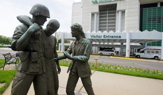 Three statues portraying a wounded soldier being helped, stand on the grounds of the Minneapolis VA Hospital, Monday, June 9, 2014. (AP Photo/Jim Mone)