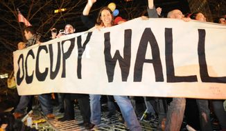 In this Saturday, Dec. 31, 2011 photo, Occupy Wall Street protesters celebrate in Zuccotti Park in New York, while standing on barricades they removed from around the park. New York City has agreed to pay nearly $600,000 to settle allegations that police wrongfully arrested a group of Occupy Wall Street protesters, marking the largest settlement to date in a single Occupy-related civil rights case, the marchers' lawyers said Tuesday, June 10, 2014.  (AP Photo/Stephanie Keith, File)
