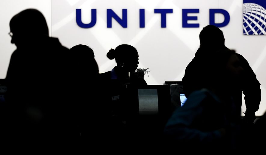 In this Saturday, Dec. 21, 2013, file photo, travelers check in at the United Airlines ticket counter at Terminal 1 in O'Hare International Airport in Chicago. (AP Photo/Nam Y. Huh, File)