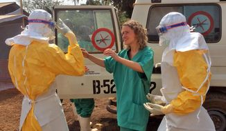 FILE - In this file photo provide byMedecins Sans Frontieres (Doctors without Borders),  taken on Friday, March 28, 2014, healthcare workers from the organization, prepare isolation and treatment areas for their Ebola, hemorrhagic fever operations, in Gueckedou, Guinea. One preacher advocated fasting and prayer to spare people from a virus that usually leads to a horrible death. Some people pray that the Ebola virus stays confined to a rural district. Others are unruffled and say the outbreak will blow over. (AP Photo/Kjell Gunnar Beraas, MSF, File)