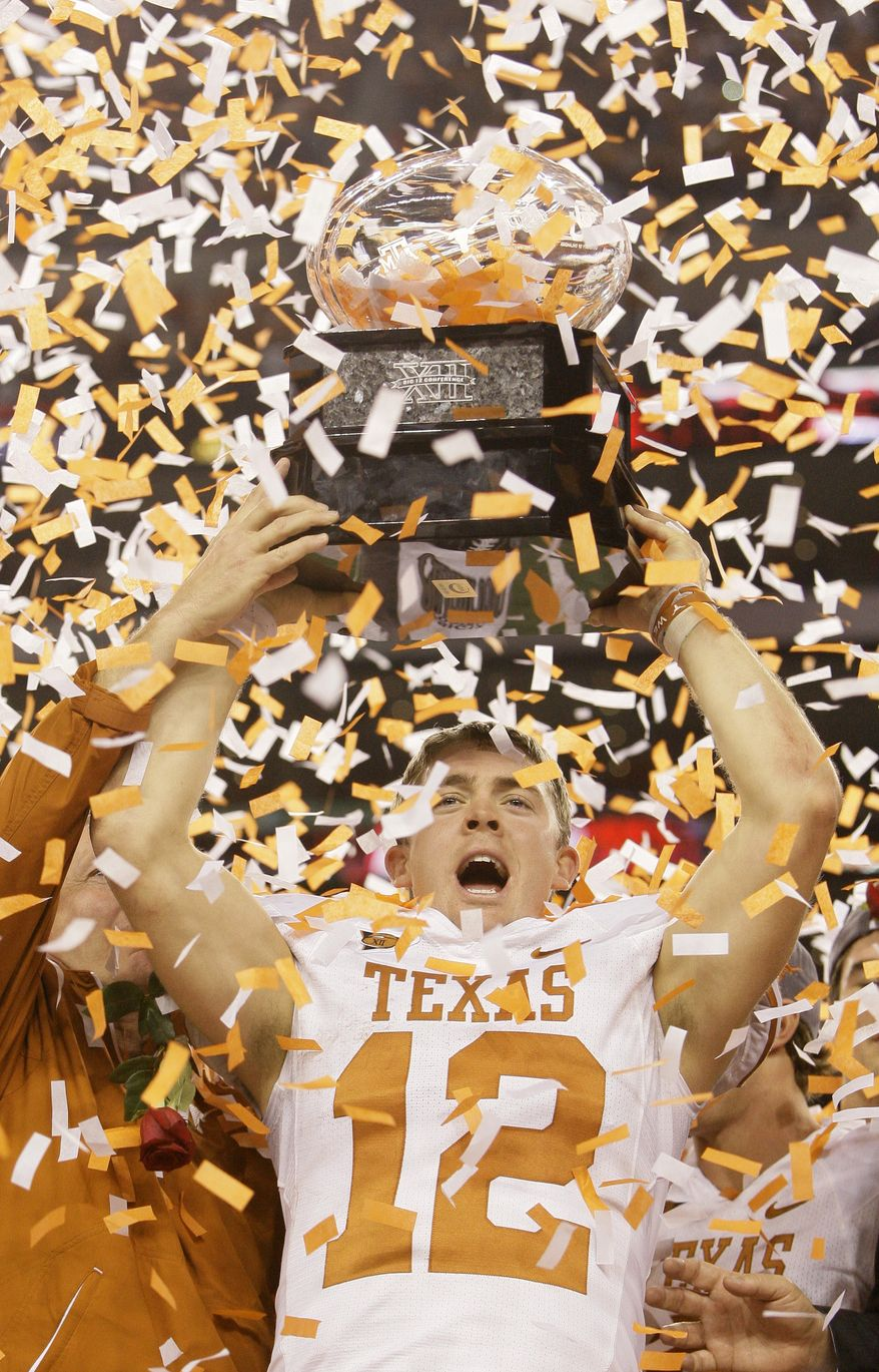 Texas quarterback Colt McCoy (12) celebrates with the trophy following their win in the NCAA college football Big 12 Conference championship game against Nebraska, Saturday, Dec. 5, 2009, in Arlington, Texas. Texas won 13-12. (AP Photo/Tony Gutierrez)