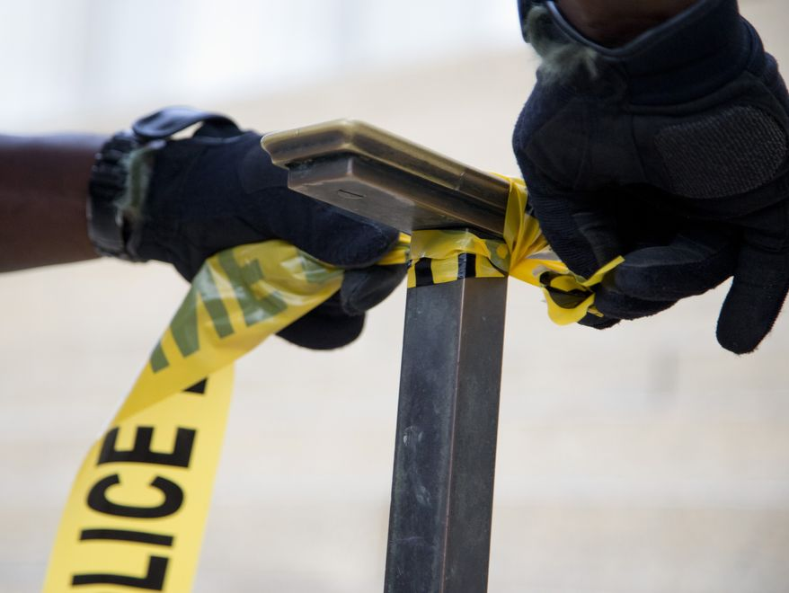 A police officer ties police tape to a handrail. (Associated Press) ** FILE **