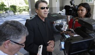 Texas Gov. Rick Perry, center, talks to reporters after driving up in a Tesla Motors Type S electric car in Sacramento, Calif., Tuesday, June 10, 2014. Perry, the former and potential 2016 Republican presidential candidate, arrived at the meeting with statewide GOP lawmakers and officials across the street from the state Capitol. He is trying to persuade Tesla Motors, based in Palo Alto, to build a $5 billion battery plant in Texas. (AP Photo/Rich Pedroncelli)
