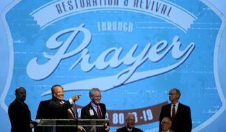 The Rev. Fred Luter Jr., at podium, president of the Southern Baptist Convention, smiles while addressing the convention during its annual meeting Tuesday, June 10, 2014, in Baltimore.   The Southern Baptists are electing a new president to succeed the Rev. Fred Luter Jr., who became the denomination's first African-American president in 2012. Contenders include the Rev. Dennis Kim, pastor of a Korean church in Silver Spring, Maryland, and the Rev. Ronnie Floyd, pastor of Cross Church, with several locations in northwest Arkansas. The Southern Baptist Convention is the nation's largest Protestant denomination, with 15.7 million members, but leaders are concerned about recent membership declines. (AP Photo/Steve Ruark)