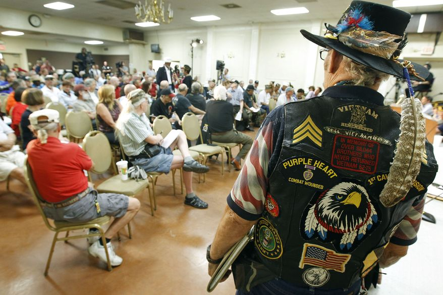 ** FILE ** Vietnam veteran Ron Silver Eagle D'Andre, right, listens during a town hall meeting at American Legion Post 1 on Monday, June 9, 2014, in Phoenix concerning health-care issues at the Phoenix VA facilities. (AP Photo/Ralph Freso)
