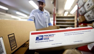 **FILE** Packages wait to be sorted in a Post Office in Atlanta on Feb. 7, 2013, as U.S. Postal Service carrier Michael McDonald gathers mail to load into his truck before making his delivery run. (Associated Press)