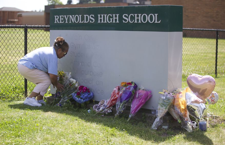 Fei Wilkening leaves flowers at a growing memorial at the entrance to Reynolds High School on Wednesday, June 11, 2014, in Troutdale, Ore. Wilkening had a daughter graduate from Reynolds four years ago. A 15-year-old boy accused of killing a fellow freshman in a locker room at the high school on Tuesday was heavily armed with an assault rifle, handgun and knife that police said Wednesday had been taken from a secured area at his family home. (AP Photo/The Oregonian, Randy L. Rasmussen)