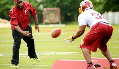 Washington Redskins running backs coach Randy Jordan, left, runs a drill during organized team activities at Redskins Park, Ashburn, Va., Wednesday, June 11, 2014. (Andrew Harnik/The Washington Times)