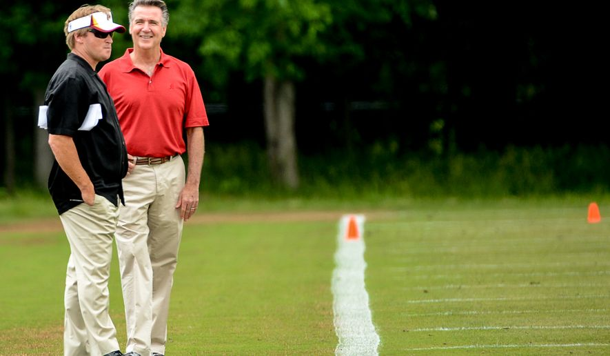 Former NFL head coach and current ESPN analyst Jon Gruden, left, talks with Washington Redskins General Manager Bruce Allen, right, on the sideline during organized team activities at Redskins Park, Ashburn, Va., Wednesday, June 11, 2014. (Andrew Harnik/The Washington Times)