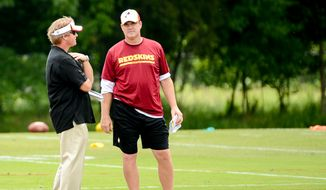 Washington Redskins head coach Jay Gruden, right, talks with his brother, former NFL head coach and current ESPN analyst Jon Gruden, left, on the sideline during organized team activities at Redskins Park, Ashburn, Va., Wednesday, June 11, 2014. (Andrew Harnik/The Washington Times)