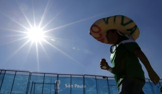 """Mexico soccer fan Edgar Gomez wears a sombrero that reads in Spanish """"Long live Mexico"""" as he heads toward Itaquerao Stadium in Sao Paulo, Brazil, before the start of the opening World Cup game in Sao Paulo, Brazil, Thursday, June 12, 2014. (AP Photo/Julio Cortez)"""