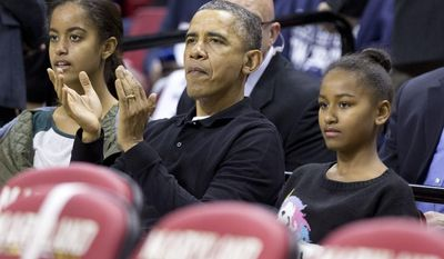 President Barack Obama, center, with his daughters Malia, left, and Sasha, right, cheers as they watch a basketball game between his  brother-in-law Oregon State Beavers Coach Craig Robinson's team play against the Maryland Terrapins, Sunday, Nov. 17, 2013, at the Comcast Center in College Park, Md. (AP Photo/Manuel Balce Ceneta)