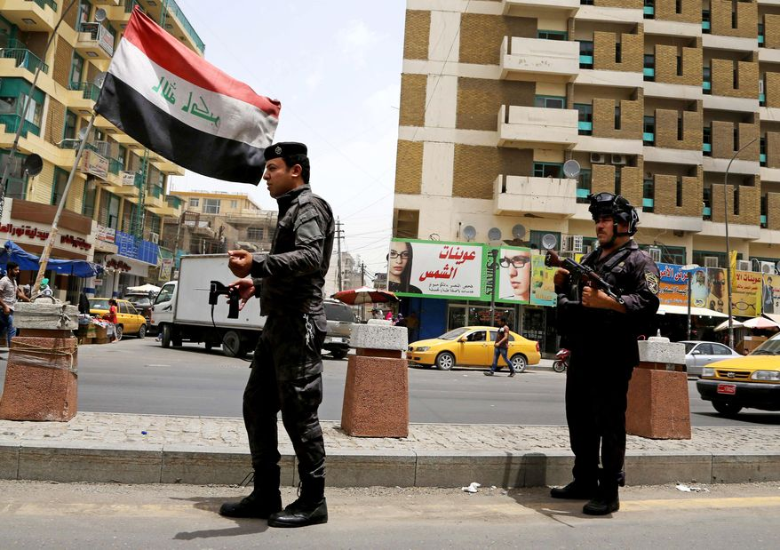 Iraqi federal policemen stand guard at a checkpoint in Baghdad, Iraq, Wednesday, June. 11, 2014. (AP Photo/ Karim Kadim)