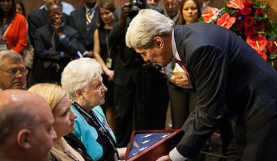 Secretary Kerry dedicated a memorial wall honoring personnel who have died while participating in overseas criminal justice and counternarcotics assistance programs on behalf of the United States during a ceremony today. Secretary Kerry presents Rebecca Bynum a flag in honor of her son, Kevin Bynum.