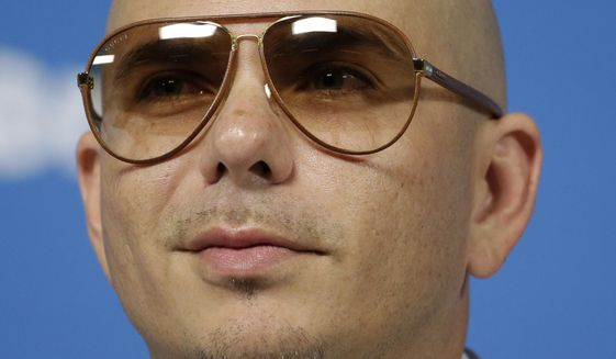 Cuban-American rapper Pitbull listens to a question during a news conference one day before the World Cup soccer tournament starts in Sao Paulo, June 11, 2014. (AP Photo/Felipe Dana) ** FILE **