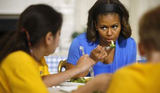 First lady Michelle Obama sits down with students and eats a salad made from vegetables harvested from the White House garden, Thursday, June 12, 2014, in the State Dining Room at the White House in Washington. (AP Photo/Charles Dharapak)