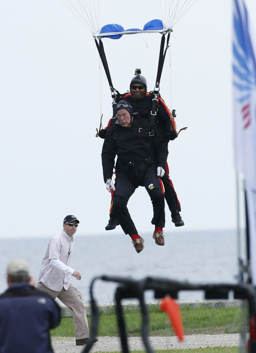 Former President George H.W. Bush, strapped to Sgt. 1st Class Mike Elliott, a retired member of the Army's Golden Knights parachute team, prepare to land on the lawn at St. Anne's Episcopal Church while celebrating Bush's 90th birthday in Kennebunkport, Maine, Thursday, June 12, 2014. (AP Photo/Robert F. Bukaty)