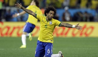Brazil's Marcelo celebrates after  Oscar scored the 3rd goal during the group A World Cup soccer match between Brazil and Croatia, the opening game of the tournament, in the Itaquerao Stadium in Sao Paulo, Brazil, Thursday, June 12, 2014.(AP Photo/Kirsty Wigglesworth)