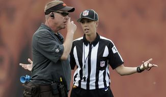 Referee trainee Sarah Thomas, right, talks to Cleveland Browns equipment manager Brad Melland during a mandatory minicamp practice at the NFL football team's facility in Berea, Ohio Thursday, June 12, 2014. Thomas, who has officiated NCAA college games, is taking part in the NFL's referee development program. (AP Photo/Mark Duncan)