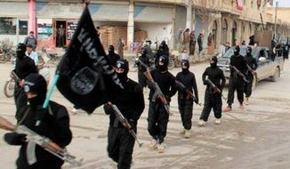 Fighters from the jihadist rebel group Islamic State of Iraq and al-Sham march in Raqqa, Syria, from an undated photo released on a jihadist website Jan. 14, 2014. (Associated Press) **FILE**