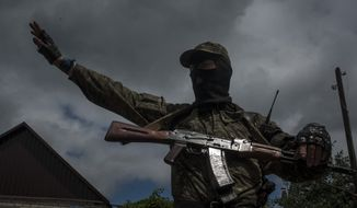 A pro-Russian fighter stands guard at a checkpoint in Slovyansk, eastern Ukraine, Thursday, June 12, 2014. The city has been an epicenter of a nearly two-month standoff between Ukrainian forces and pro-Russian rebels, who have seized administrative buildings, police stations and border posts across the region. (AP Photo/Evgeniy Maloletka)