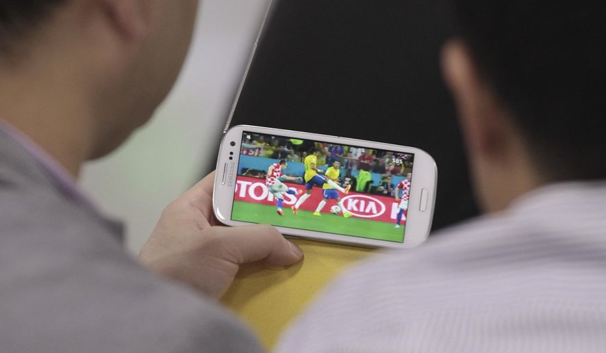 Men watch a smartphone broadcasting the World Cup opening match between Brazil and Croatia at Seoul Railway Station in Seoul, South Korea, Friday, June 13, 2014. (AP Photo/Ahn Young-joon)