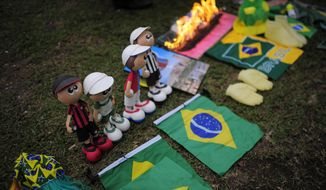 Materials belonging to witchdoctor Chik Jeitoso are displayed on a patch of grass outside the Arena da Baixada stadium in Curitiba, Brazil, Wednesday, June 11, 2014. During the performance Jeitoso, a famous witchdoctor from Curitiba, predicted difficulties for Brazil in the World Cup and that the bad energies are likely to affect Neymar and Messi during the competition. (AP Photo/Manu Fernandez) ** FILE **