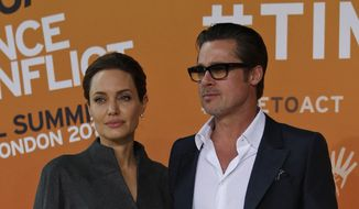 US actress Angelina Jolie, left, Special Envoy of the United Nations High Commissioner for Refugees, accompanied by her partner and US actor Brad Pitt pose for the photographers as they arrive at the 'End Sexual Violence in Conflict' summit in London, Friday, June 13, 2014. (AP Photo/Lefteris Pitarakis) ** FILE **