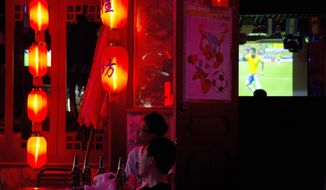 Chinese soccer fans watch the opening match of the 2014 World Cup between Brazil and Croatia, at a bar in Beijing, China, Friday, June 13, 2014. (AP Photo/Ng Han Guan)