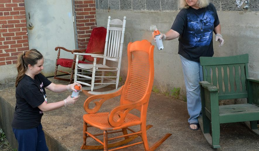 Kyla Nichols, left, Program director for YWCA's Shanklin Center Elder Abuse Program, and Erin Turner, YWCA's Director of Retail, paint rocking chairs Tuesday, June 10, 2014, in preparation for Elder Abuse Awareness Day / Month. YWCA staff  be putting the rockers around town on Friday. (AP Photo/The Charleston Gazette, Chris Dorst)