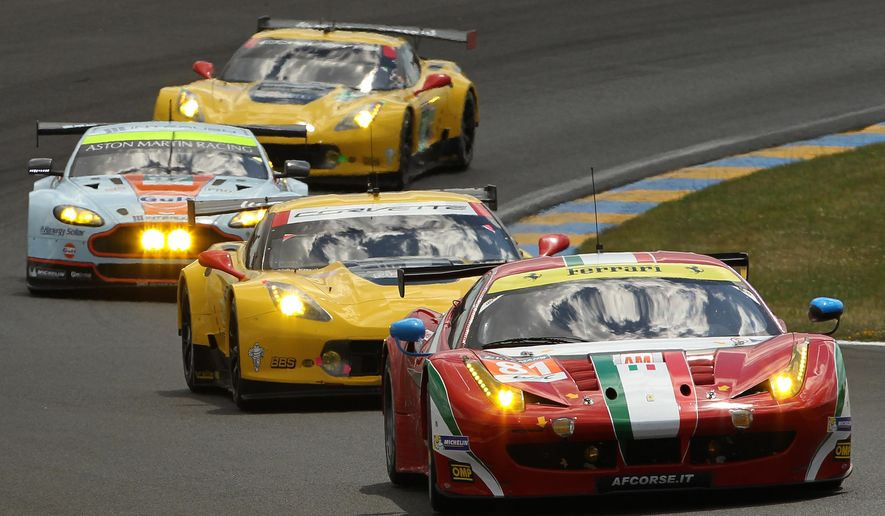The Ferrari 458 Italia, front, driven by Britain's Sam Bird, Italy's Michele Rugolo and Australia's Stepan Wyatt during the 82nd 24-hour Le Mans endurance race, in Le Mans, western France, Saturday, June 14, 2014. (AP Photo/Bob Edme)