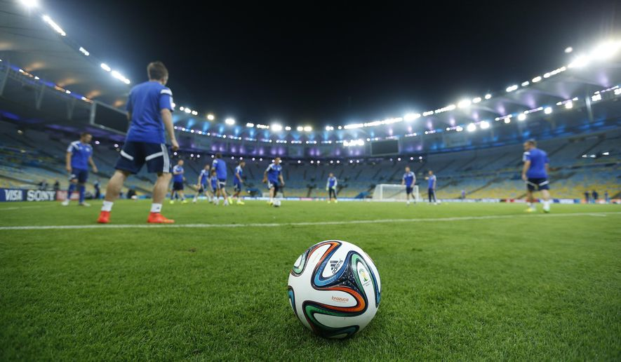 A 2014 World Cup official soccer ball, called Brazuca, sits on the sidelines as Bosnia-Herzegovina players pass the ball, background, during a training session at the Maracana Stadium in Rio de Janeiro, Brazil, Saturday, June, 14, 2014. Bosnia-Herzegovina will face Argentina in group F of the 2014 soccer World Cup at the stadium on Sunday. (AP Photo/Victor R. Caivano) ** FILE **