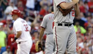 Washington Nationals starting pitcher Jordan Zimmermann, right, rubs up a new ball as St. Louis Cardinals' Matt Adams rounds the bases after hitting a solo home run during the second inning of a baseball game on Friday, June 13, 2014, in St. Louis. (AP Photo/Jeff Roberson)