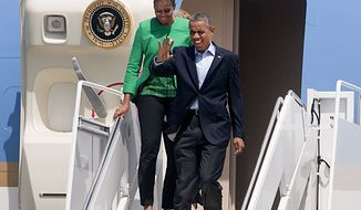 U.S. President Barack Obama and First Lady Michelle Obama exit Air Force One in Bismarck, N.D. June 13, 2014 after arriving on Air Force One there for his trip to the Standing Rock Indian Reservation in Cannon Ball, North Dakota.  (AP Photo/Bruce Crummy)