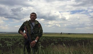 A pro-Russian fighter guards the site of remnants of a downed Ukrainian army aircraft Il-76 at the airport near Luhansk, Ukraine, Saturday, June 14, 2014. Pro-Russian separatists shot down the military transport plane Saturday in the country's restive east, killing all 49 service personnel on board, Ukrainian officials said. (AP Photo/Evgeniy Maloletka)