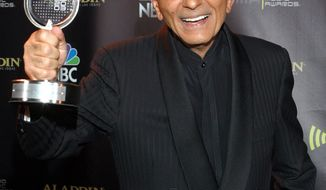 """** FILE ** In this Oct. 27, 2003, file photo, Casey Kasem poses for photographers after receiving the Radio Icon award during """"The 2003 Radio Music Awards"""" at the Aladdin Resort and Casino in Las Vegas. Kasem, the smooth-voiced radio broadcaster who became the king of the top 40 countdown, died Sunday, June 15, 2014, according to Danny Deraney, publicist for Kasem's daughter, Kerri. He was 82. (AP Photo/Eric Jamison, file)"""