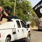 This image posted on a militant website on Saturday, June 14, 2014, which has been verified and is consistent with other AP reporting, appears to show militants from the al-Qaida-inspired Islamic State of Iraq and the Levant (ISIL) with truckloads of captured Iraqi soldiers after taking over a base in Tikrit, Iraq.  (AP Photo via militant website)