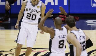 San Antonio Spurs guard Manu Ginobili (20), guard Patty Mills (8) and center Tiago Splitter (22) celebrate against the Miami Heat during the second half in Game 5 of the NBA basketball finals on Sunday, June 15, 2014, in San Antonio. (AP Photo/Tony Gutierrez)