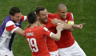 Switzerland's Haris Seferovic, second from right, celebrates scoring his side's second goal with teammates during the group E World Cup soccer match between Switzerland and Ecuador at the Estadio Nacional in Brasilia, Brazil, Sunday, June 15, 2014. Switzerland defeated Ecuador 2-1. (AP Photo/Themba Hadebe)