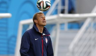 United States' head coach Jurgen Klinsmann heads a soccer ball before an official training session the day before the group G World Cup soccer match between Ghana and the United States at the Arena das Dunas in Natal, Brazil, Sunday, June 15, 2014.  (AP Photo/Julio Cortez)