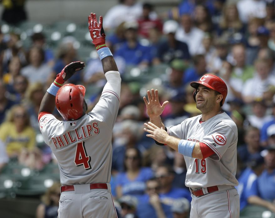 Cincinnati Reds' Brandon Phillips (4) gets a high-five from teammate Joey Votto after hitting a two-run home run during the first inning of a baseball game against the Milwaukee Brewers, Sunday, June 15, 2014, in Milwaukee. (AP Photo/Jeffrey Phelps)